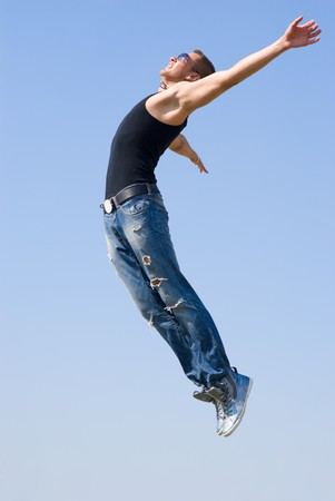acrobat: Athlete man with teeth smile and open arms fly to the sun. He wears sun glasses