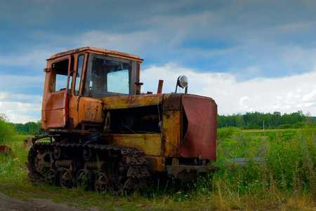 An old but still working agricultural machine under the moody sky photo