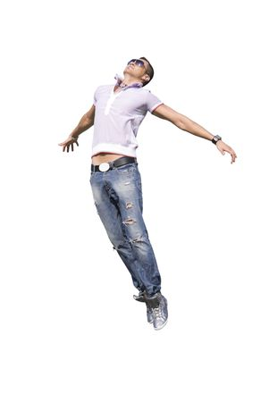 The young man in jeans is flying up with open arms. He has sun glasses and earring. Isolated on white background