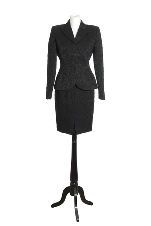 Female mannequin torso in black classic female suit. Isolated on white background