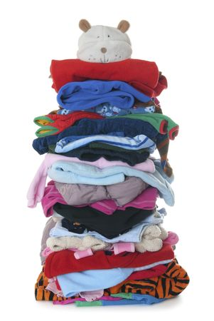 Huge pile (height 1 meter) made of childrens textile clothes. Isolated on white background