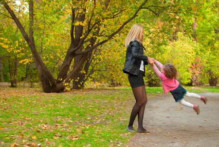 Mom is spining around with her daughter (3 years old) in autumn park. Standard-Bild