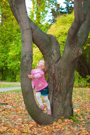 3 month: Little girl (3 years old) leaned to a tree and is looking up with surprise