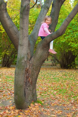 stitting: Little girl (3 years old) is  smiling and stitting on a tree branch. She is looking at the camera