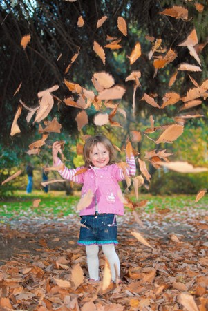 Little girl (3 years old) is playing with autumn leaves in park Stock Photo - 7904314