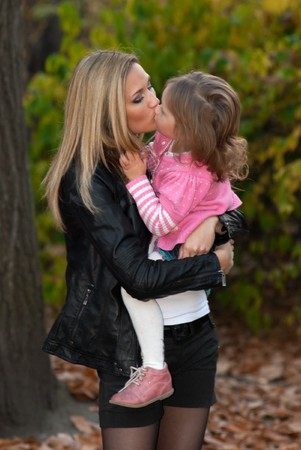 Long haired mother kisses her daughter in autumn park.