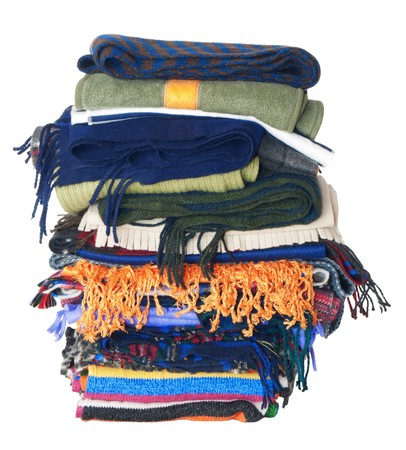 Pile of winter woollen scarfs. Isolated on white background photo