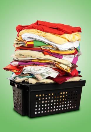Colorful stack of bed-clothes in plastic crate. photo