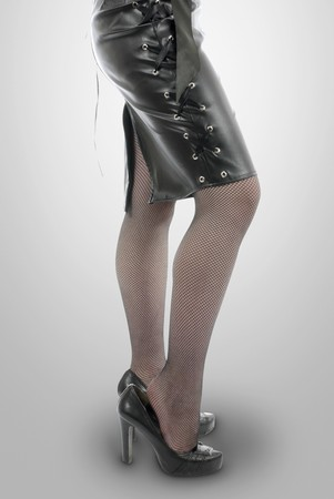 high heels woman: emale legs in stockings on high heels. Woman wears leather skirt with lacing and shows one hand with ring. Isolated on white background