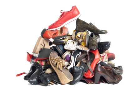 Huge pile of female and male second-hand shoes. Isolated on white background