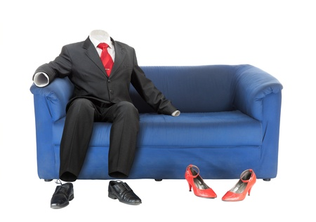 Classic empty male suit is sitting on blue textile couch near red female shoes. Conceptual photo. Isolated over white Stock Photo - 8488702