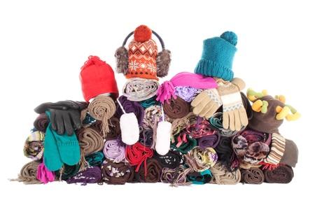 woolen fabric: Enorme pila de invierno lana bufandas, gorros y guantes. Aislado en blanco Foto de archivo