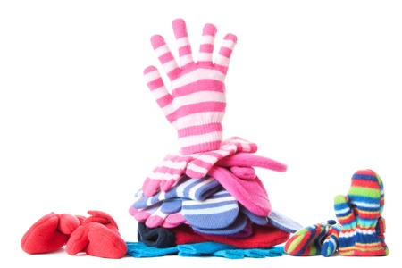 personal accessory: Pile of woollen garments and pink glove in greeting gesure at the top. Isolated over white