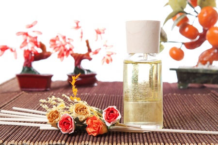 Glass bottle with yellow oil and small flowers lay on brown mat. Stone trees at the background