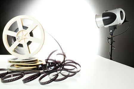 Stack of old 8mm film tapes and studio flashlight lighten the background. photo