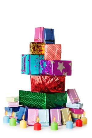 Colorful stack of gift boxes and candles isolated over white background Stock Photo