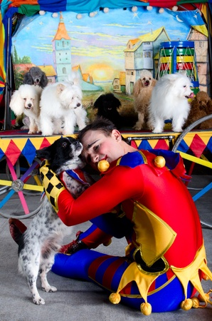 Harlequin clown in depression embrace his small dog. At the backround group of dogs and painting of the old town photo