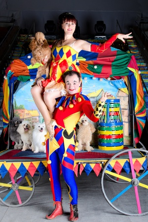 Smiling Harlequin holding Colombina on his shoulders. She carries small red poodle. At the background group of dogs and retro carriage photo