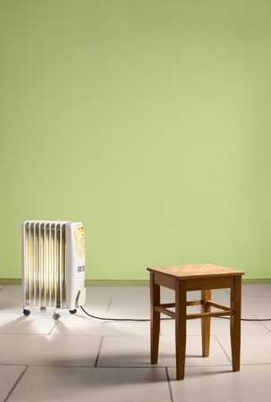 Empty room with heating electricity radiator and wooden chair. Green walls and stone tiles on the floor.