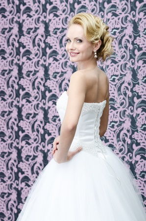 20s yeared bride in white dress is looking back over the shoulder with smile on her face photo