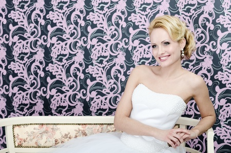 20s yeared bride in white wedding dress is sitting on a bencs hear the colorful wall Standard-Bild
