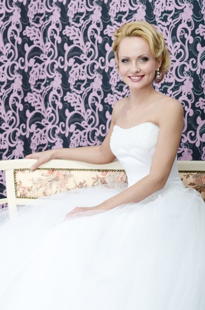 Studio shot of the middle aged caucasian bride  She is sitting on the bench with smile on her face photo