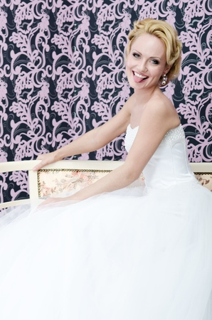 20s aged young adult bride is sitting on a bench  She is smiling and put out her tongue  photo