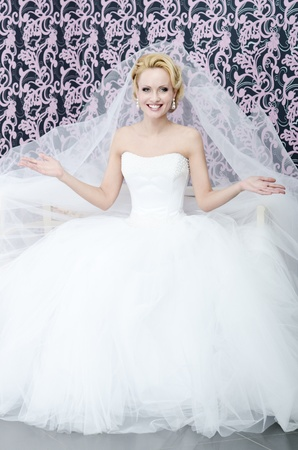 20s aged young adult bride is sitting on a bench  She is smiling and her arms are opened  photo
