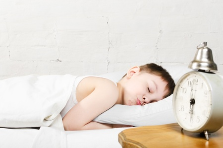 alarming: Small toddler boy  4 years old  is sleeping in bed  Old clock show 6 o