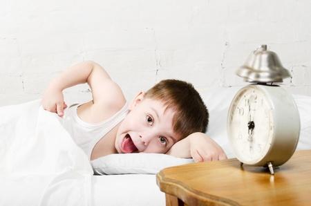 despertarse: Ni�o peque�o ni�o de 4 a�os est� acostado en la cama y mostrando la lengua �l est� mirando a la c�mara Antiguo reloj de espect�culo o 6