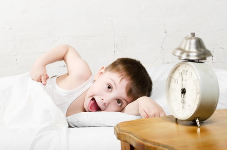 Small toddler boy  4 years old  is lying in bed and showing tongue  He is looking at the camera  Old clock show 6 o
