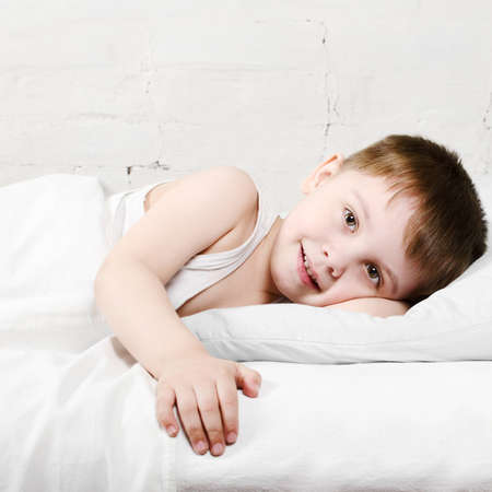 Small toddler boy  4 years old  is lying in bed and smiling  He is looking at the camera photo