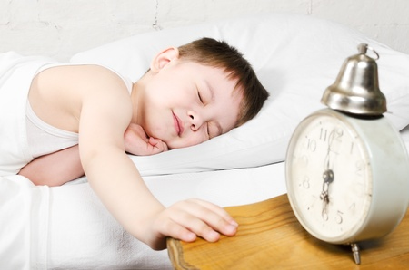 Small toddler boy  4 years old  is sleeping in bed  Old clock show 6 o