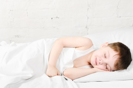 bedtime: Small boy  4 years  is sleeping near the bright brick wall Stock Photo
