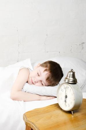 Kleine Kleinkind Junge (4 Jahre) im Bett schlafen. Backsteinmauer im Hintergrund. Alte Uhr zeigt 06.00 Uhr.