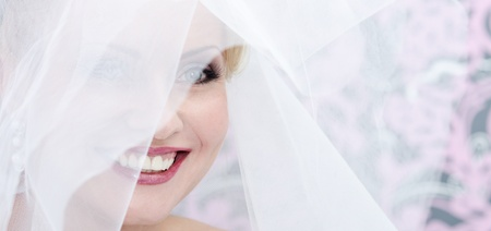Close up image of the smiling adult bride  Transparent veil cover her face photo