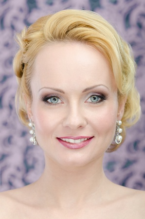 Close up portrait of the smiling yount adult blonde with make-up and hair style  Hi end retouch photo