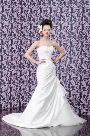 Full length portrait of the young adult bride with lily flowers in hair photo