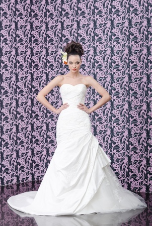 Young adult bride in white wedding dress posing over magenta wall  Stock Photo - 12897345