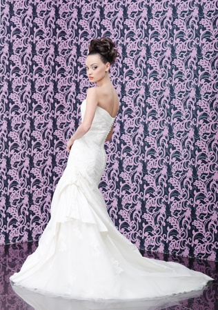 Young adult bride in white wedding dress posing over magenta wall  photo