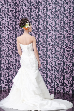 Young adult bride in white wedding dress posing over magenta wall  Her hair decorated with lily flowers photo
