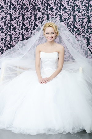 20 yeared bride in white wedding dress with veil is smiling and sitting on a bench photo