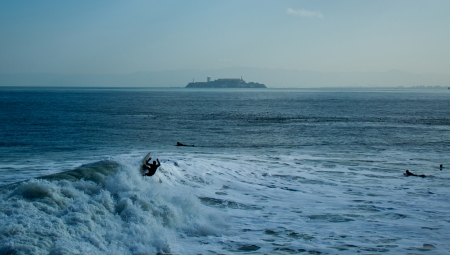a few surfers on the San Francisco Bay, in front of the Isle of Alcatraz photo