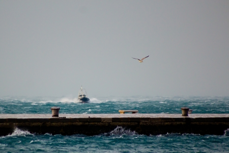 very windy: a boat approaching the harbour of Trieste in a very windy day Stock Photo