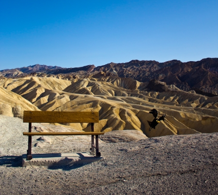 An empty Bench and a Raven flying at Zabriskie Point, Nevada photo