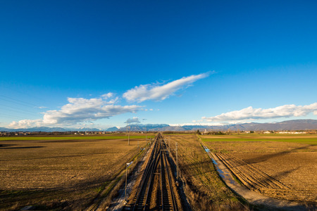 a railway through the fields in direction of mountains of Friuli Venezia-Giulia, Italy photo