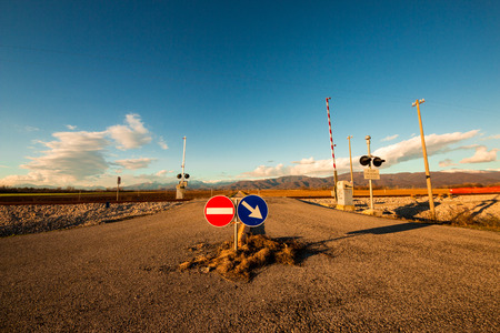 an isolated railroad crossing in the plan of Friuli Venezia-Giulia  Mountains behind  photo