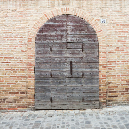 an old door in the middle of a medieval village of Italy photo