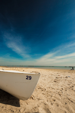 a white boat on the beach on a sunny summer morning photo