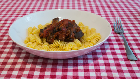 a tipical dish of the italian cousine, a sicilian plate of pasta alla norma, with eggplant and tomato photo